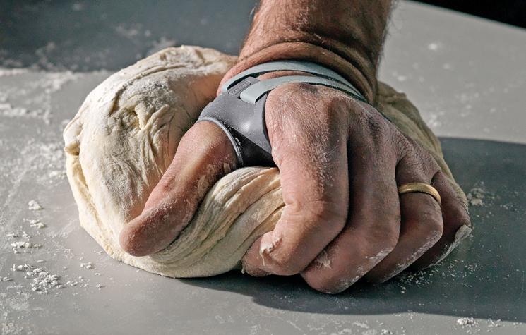 hand kneading dough while wearing the Push MetaGrip Thumb Brace